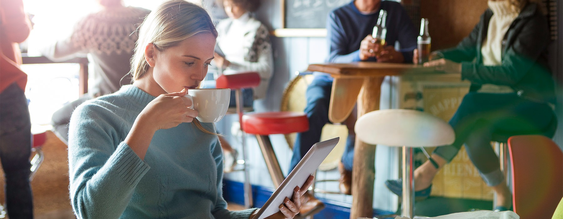 A Woman enjoying a cup of coffee and reading an ipad.